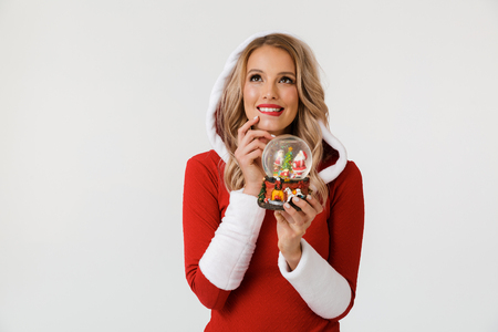 Portrait of a wishful blonde woman dressed in red New Year costume standing isolated over white background, holding snowball Stock Photo
