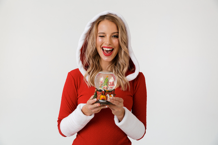 Portrait of a joyful blonde woman dressed in red New Year costume standing isolated over white background, holding snowball, winking