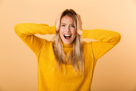 Portrait of an annoyed young woman dressed in sweater standing isolated over yellow background, screaming, looking up