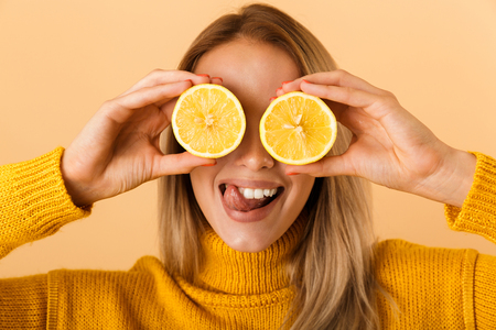 Photo of a beautiful woman covering eyes with citrus lemons posing isolated over yellow wall background.