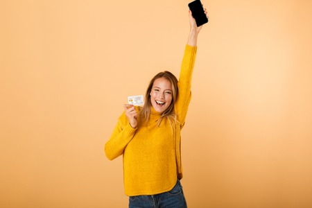 Portrait of a smiling young woman dressed in sweater standing isolated over yellow background, showing credit card, using mobile phone, celebrating