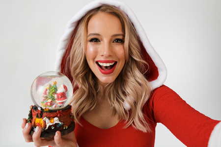 Close up portrait of a cheerful blonde woman dressed in red New Year costume standing isolated over white background, holding snowball, taking a selfie