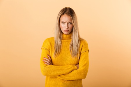 Portrait of an upset young woman dressed in sweater standing isolated over yellow background, holding arms folded