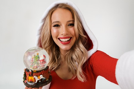 Close up portrait of a happy blonde woman dressed in red New Year costume standing isolated over white background, holding snowball, taking a selfie Stock Photo