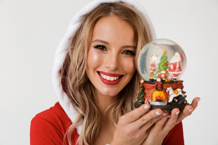 Close up portrait of a smiling blonde woman dressed in red New Year costume standing isolated over white background, holding snowball Stock Photo