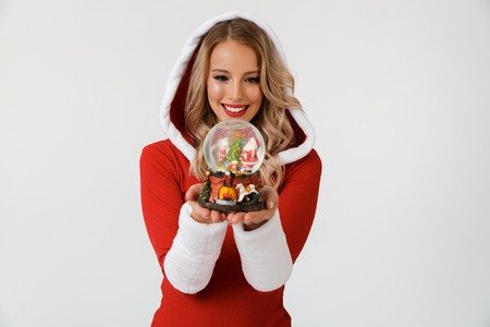 Portrait of a cheerful blonde woman dressed in red New Year costume standing isolated over white background, holding snowball