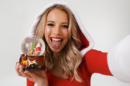 Close up portrait of a funny blonde woman dressed in red New Year costume standing isolated over white background, holding snowball, taking a selfie