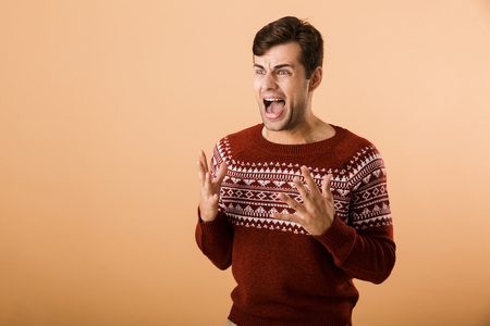 Image of caucasian man 20s with stubble wearing knitted sweater screaming and expressing outrage isolated over beige background