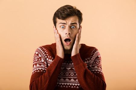Image of intimidated man 20s with stubble wearing knitted sweater screaming and touching face isolated over beige background