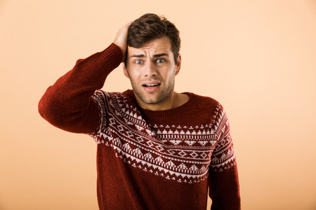 Image of uptight man 20s with stubble wearing knitted sweater grabbing head isolated over beige background Stock Photo