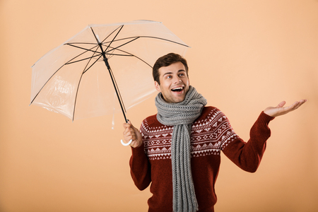 Portrait a delighted young man dressed in sweater and scarf isolated over beige background, standing under umbrella Standard-Bild - 112726600