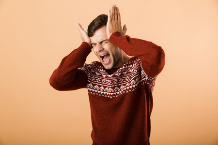 Image of frustrated man 20s with stubble wearing knitted sweater screaming and grabbing head isolated over beige background Stock Photo