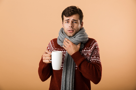 Portrait a sick man dressed in sweater and scarf isolated over beige background, holding cup of hot tea