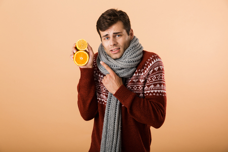 Portrait a sick man dressed in sweater and scarf isolated over beige background, holding sliced oranges