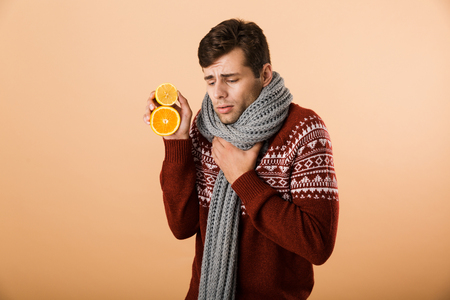 Portrait an ill man dressed in sweater and scarf isolated over beige background, holding sliced oranges