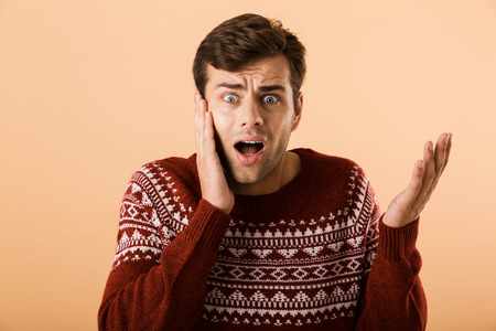 Image of confused man 20s with stubble wearing knitted sweater screaming and touching face isolated over beige background Stock Photo