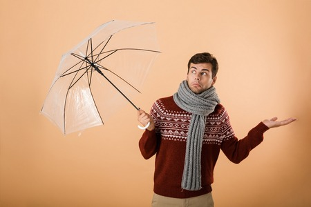 Portrait a confused young man dressed in sweater and scarf isolated over beige background, standing under umbrella