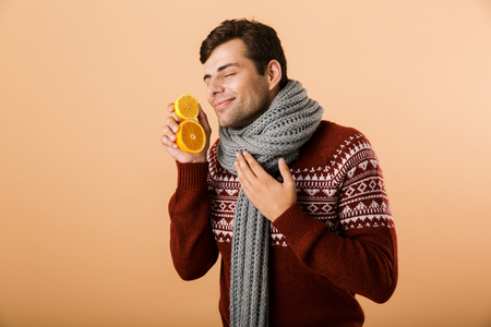 Portrait a delighted man dressed in sweater and scarf isolated over beige background, holding sliced oranges
