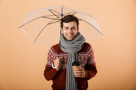 Portrait a satisfied young man dressed in sweater and scarf isolated over beige background, standing under umbrella, holding coffee cup