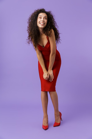 Full length image of cheerful woman 20s wearing red dress smiling at camera isolated over violet background Stock Photo