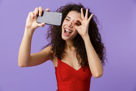 Image of elegant woman 20s wearing red dress taking selfie photo on black smartphone standing isolated over violet background Stock Photo