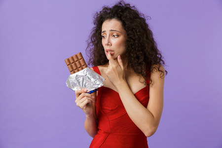 Image of elegant woman 20s wearing red dress holding chocolate bar standing isolated over violet background Stock Photo - 112726933