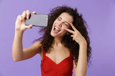 Image of glamour woman 20s wearing red dress taking selfie photo on black cell phone standing isolated over violet background