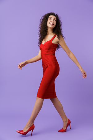 Full length image of beautiful woman 20s wearing red dress smiling and walking isolated over violet background