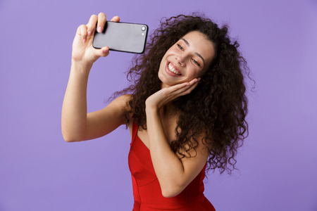 Image of pretty woman 20s wearing red dress taking selfie photo on black mobile phone standing isolated over violet background
