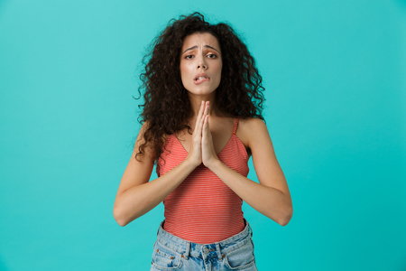 Image of curly woman 20s wearing casual holding palms together standing isolated over blue background Stock Photo