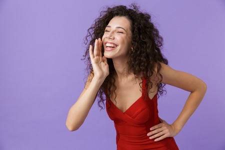 Portrait of a smiling woman with dark curly hair wearing red dress isolated over violet background, shouting loud