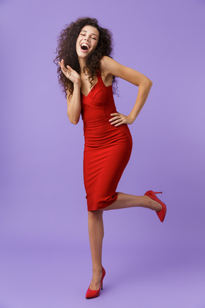 Full length image of young woman 20s wearing red dress smiling at camera isolated over violet background