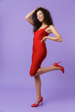 Full length image of seductive woman 20s wearing red dress smiling at camera isolated over violet background Stock Photo