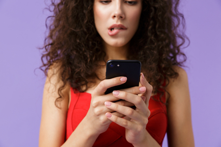 Image of cute woman 20s wearing red dress holding black smartphone standing isolated over violet background