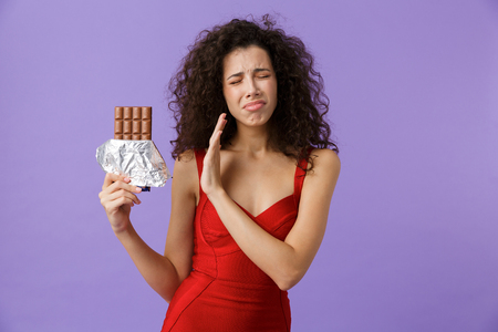 Image of displeased woman 20s wearing red dress holding chocolate bar standing isolated over violet background