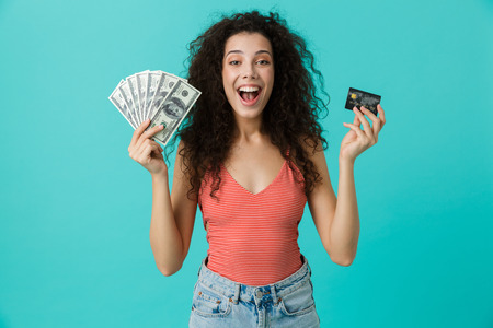 Image of lucky woman 20s wearing casual clothing holding fan of dollar money and credit card standing isolated over blue background