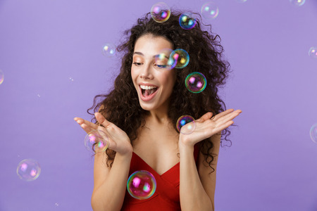 Image of young woman 20s wearing red dress laughing and standing under falling soap bubbles isolated over violet background Stock Photo