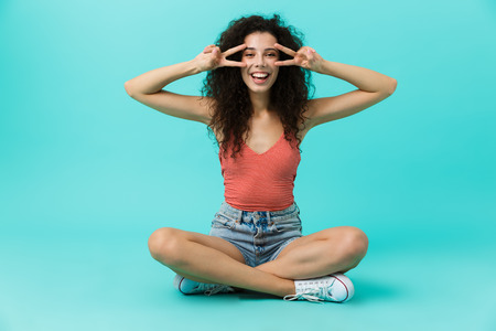 Image of charming woman 20s wearing casual clothing laughing while sitting on floor with legs crossed isolated over blue background
