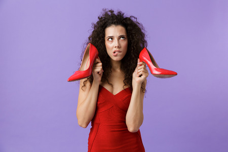 Image of caucasian woman 20s wearing red dress holding high heels shoes standing isolated over violet background Stock Photo