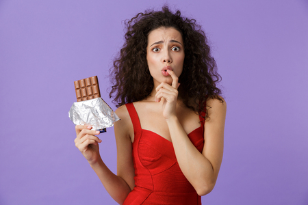 Image of excited woman 20s wearing red dress holding chocolate bar standing isolated over violet background