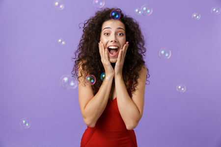 Image of charming woman 20s wearing red dress laughing and standing under falling soap bubbles isolated over violet background Stock Photo