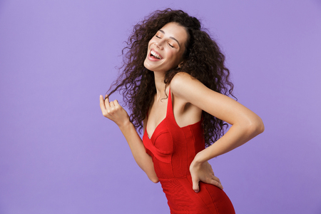 Image of european woman 20s wearing red dress smiling and dancing isolated over violet background