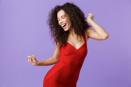Image of joyful woman 20s wearing red dress smiling and dancing isolated over violet background