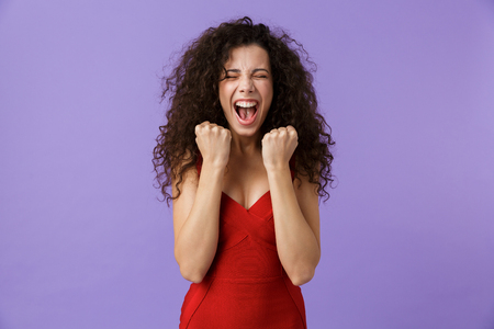Portrait of a cheerful woman with dark curly hair wearing red dress isolated over violet background, celebrating success