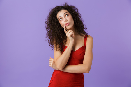 Portrait of a pensive woman with dark curly hair wearing red dress isolated over violet background, looking away 写真素材