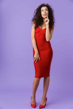 Full length image of fashionable woman 20s wearing red dress looking upward isolated over violet background Stock Photo