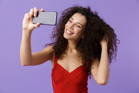 Image of curly woman 20s wearing red dress taking selfie photo on black smartphone standing isolated over violet background Stock Photo