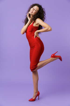 Full length image of glamour woman 20s wearing red dress smiling at camera isolated over violet background