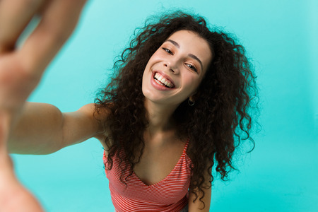 Image of gorgeous woman 20s wearing casual clothing laughing while taking selfie photo standing isolated over blue background Stock Photo
