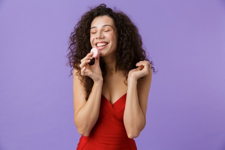 Portrait of a smiling woman with dark curly hair wearing red dress isolated over violet background, eating macaroon